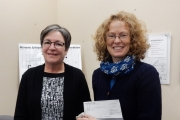 Kathleen Hill receives $100 on behalf of the Rossland Mountain Market.